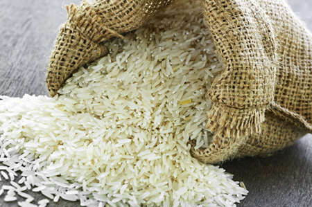 basmati: Raw long grain white rice grains in burlap bag