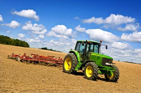 ploegen: Kleinschalige landbouw met trekker en plow in veld