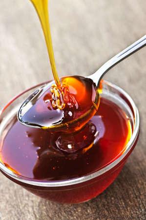 jarabe: Miel de oro gruesa llovizna en cuchara y Bol