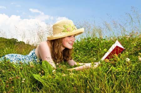 straw hat: Libro di lettura giovane adolescente in estate prato con cappello di paglia