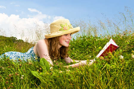 straw hat: Young teenage girl reading book in summer meadow with straw hat