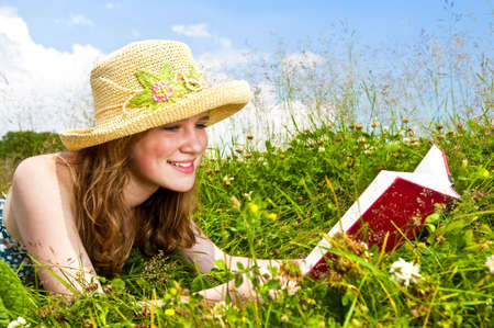 Portrait of teenage girl reading book in summer meadow with straw hat photo