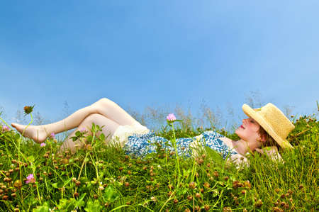 Young teenage girl laying barefoot on summer meadow in straw hat photo