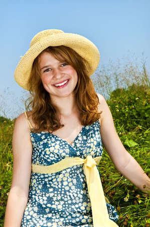Young teenage girl sitting on summer meadow in straw hat Reklamní fotografie