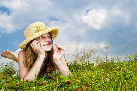Young teenage girl laying in summer meadow resting chin on hand smelling flower Stock Photo - 6243751