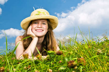 Young teenage girl laying in summer meadow resting chin on hand in straw hat photo