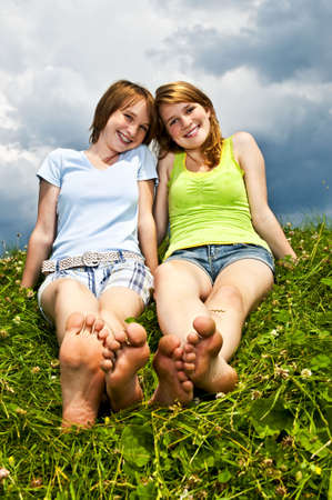 Two young teenage girl friends sitting barefoot on summer meadow photo