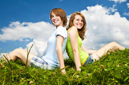 Two young teenage girl friends sitting back-to-back on summer meadow photo