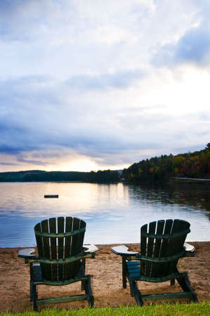 adirondack chair: Two wooden chairs on beach of relaxing lake at sunset Stock Photo