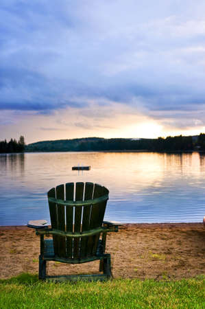 ontario: Wooden chair on beach of lake at sunset