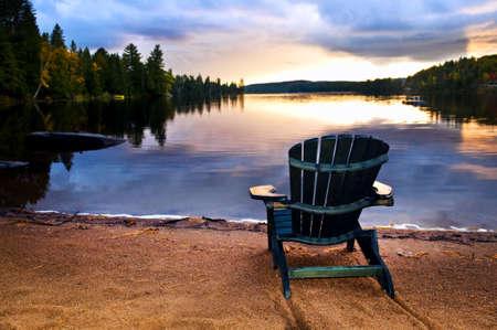 casa de campo: Silla de madera en la playa de Lago relajante al atardecer Foto de archivo