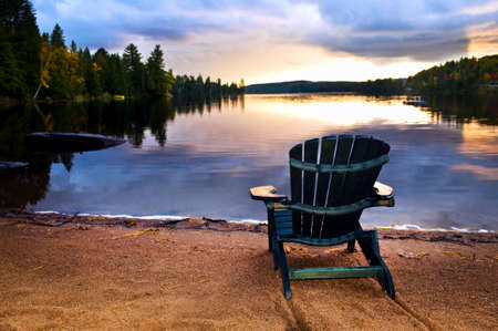 serenity: Wooden chair on beach of relaxing lake at sunset
