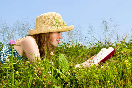 lay: Young teenage girl reading book in summer meadow with straw hat