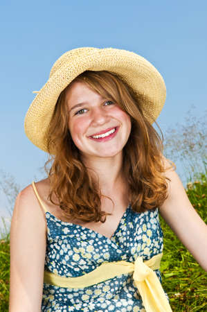 Portrait of young teenage girl smiling in summer meadow with straw hat photo