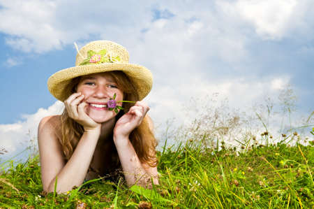Young teenage girl laying in summer meadow resting chin on hand holding flower photo