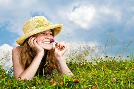 夏の草原の香りの花の手にあごを休憩に敷設若い 10 代の少女 写真素材