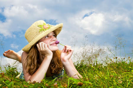 Young teenage girl laying in summer meadow resting chin on hand smelling flower photo