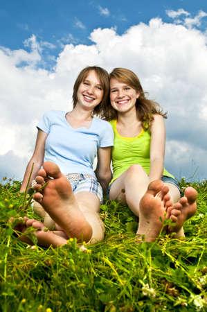 Twee jonge tiener meisje vrienden zitten barefoot op zomer meadow Stockfoto