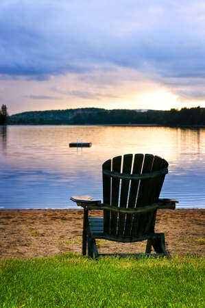 adirondack chair: Wooden chair on beach of lake at sunset
