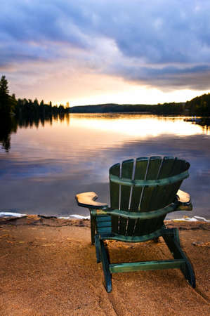Wooden chair on beach of relaxing lake at sunset photo