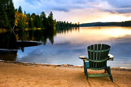 algonquin park: Wooden chair on beach of relaxing lake at sunset