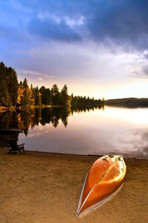 Canoe on beach at sunset on lake shore