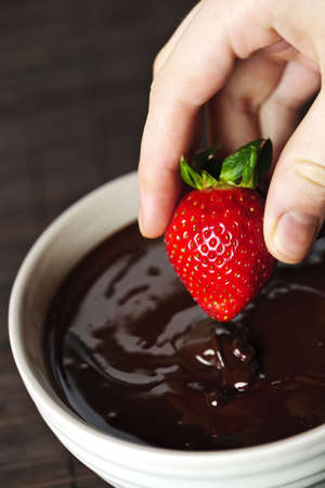 Hand dipping fresh strawberry in melted chocolate Stock Photo - 6278618