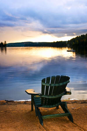 adirondack chair: Wooden chair on beach of relaxing lake at sunset