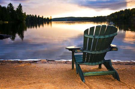 silla de madera: Silla de madera en la playa de Lago relajante al atardecer Foto de archivo