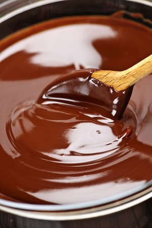Wooden spoon stirring soft melted rich chocolate photo