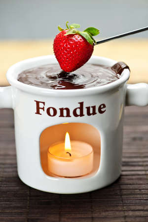 Strawberry dipped in delicious melted chocolate fondue photo