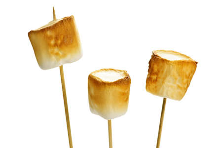 toasted: Three golden toasted marshmallows on wooden skewers Stock Photo