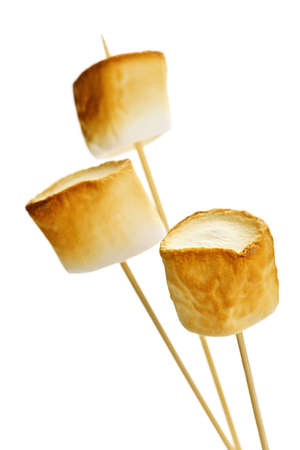 Three golden toasted marshmallows on wooden skewers Imagens