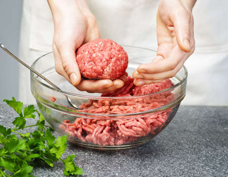 Chef making hamburgers in kitchen with ground beef photo