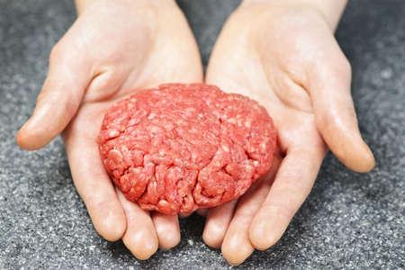 Chef making hamburger patty in kitchen with ground beef photo