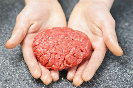 in ground: Chef rendendo hamburger patty in cucina con carne tritata