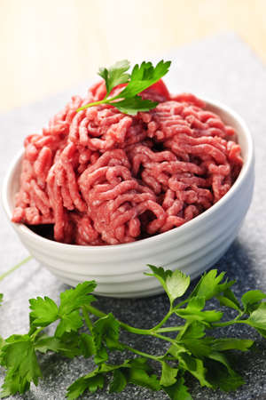 mince: Close up en el plato de carne magra picada cruda rojo