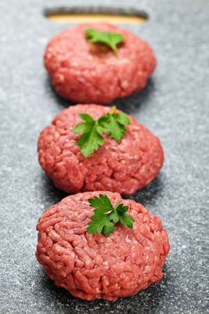 Three ground beef hamburger patties on cutting board Archivio Fotografico