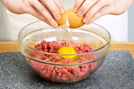 minced beef: Chef cracking egg into bowl of ground beef