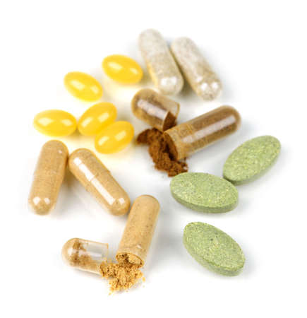 herbology: Mix of  herbal supplements and vitamin pills isolated on white