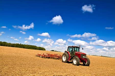 트랙터와 쟁기가있는 소규모 농업
