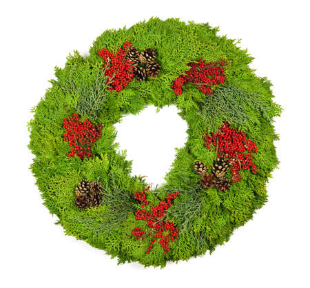 Green Christmas wreath with pine cones and berries isolated on white photo