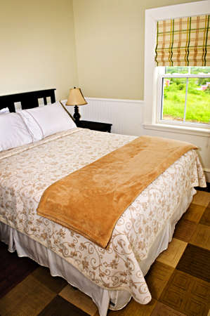 Bedroom interior with comfortable queen size bed with view photo