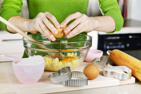 glass cutter: Cracking egg into mixing bowl making cookies Stock Photo