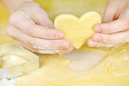 Making heart shaped shortbread cookies with cutters photo
