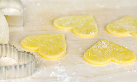 wood cutter: Making heart shaped shortbread cookies with cutters Stock Photo