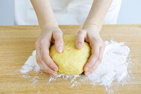 amasando: Manos amasando bola de masa con harina a bordo de corte