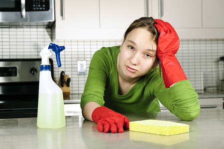 Tired girl doing kitchen cleaning chores with rubber gloves photo