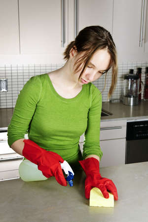 Girl cleaning kitchen with sponge and rubber gloves photo