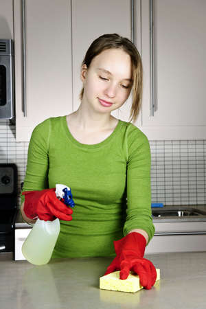 disinfecting: Girl cleaning kitchen with sponge and rubber gloves Stock Photo